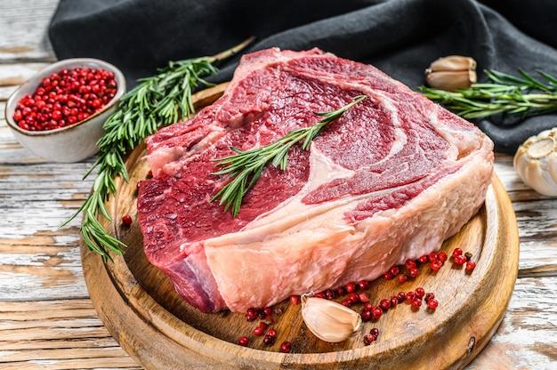 Bife de vaqueiro cru ou lombo no osso em uma tábua na carne de mármore na mesa de madeira branca