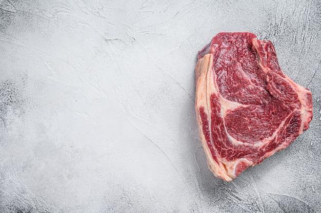 Bife de vaqueiro cru ou olho de lombo no osso na carne de mármore na mesa cinza.