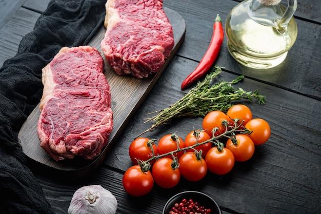 Bife de veias, carne crua de boi marmorizada, na mesa de madeira preta