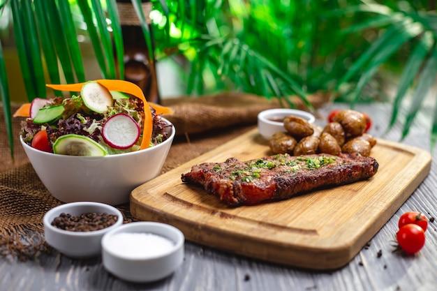 Bife de vista lateral com batatas assadas e salada de legumes