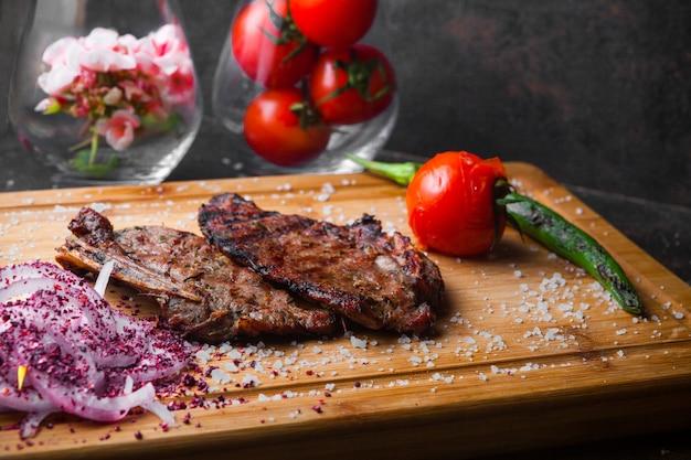 Bife de vista lateral com tomate e cebola na tábua de carne