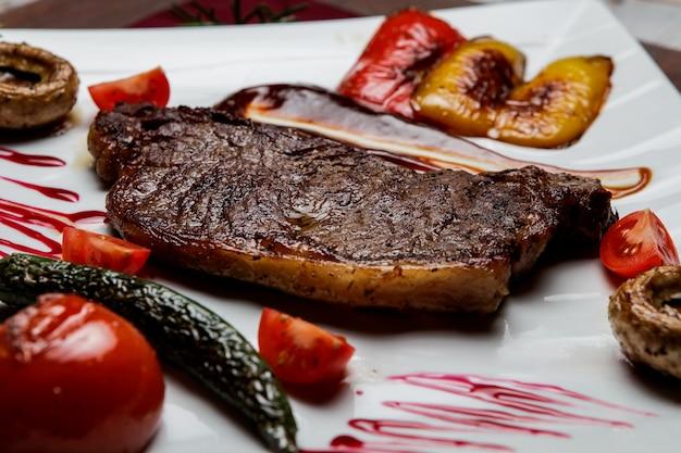 Bife de vista lateral com tomate e cogumelos fritos e pimentão frito em chapa branca na mesa de madeira