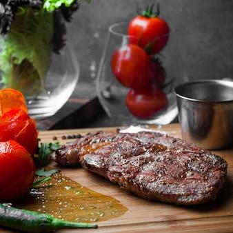 Bife de vista lateral com tomate e papel e molho picante na placa de bife