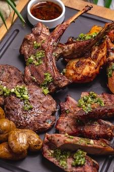 Bife de vista superior com costelas fritas com frango frito e batatas em uma placa com molho