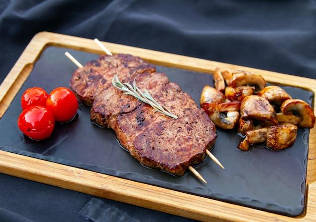 Bife de vitela grelhada com cogumelos e tomates grelhados em uma tábua