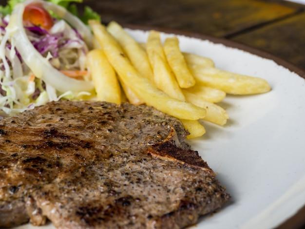 Bife do lombo com sal e pimenta, batatas fritas douradas e vegetais verdes. em branco plat