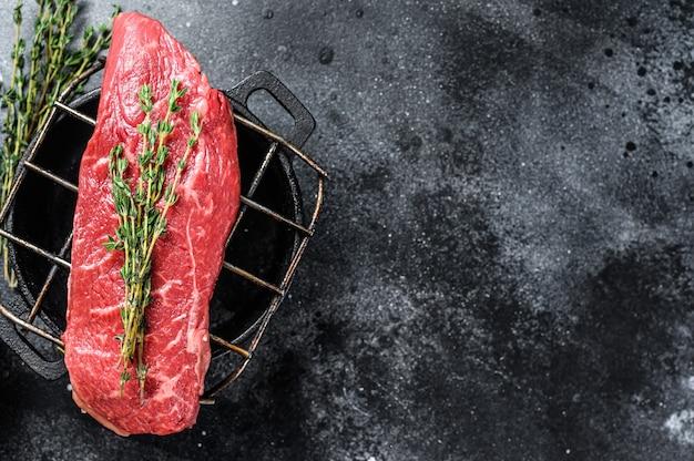 Bife do lombo cru, carne bovina. fundo de madeira escuro.