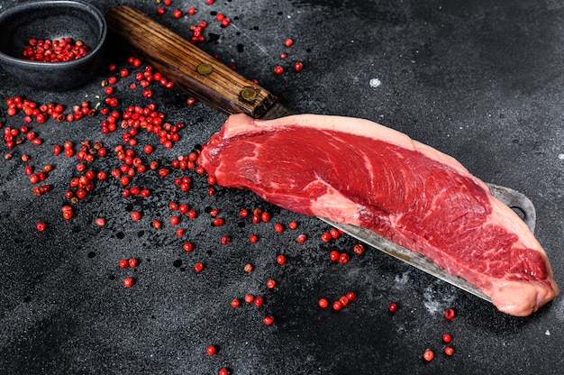 Bife do lombo cru em um cutelo. carne de mármore.