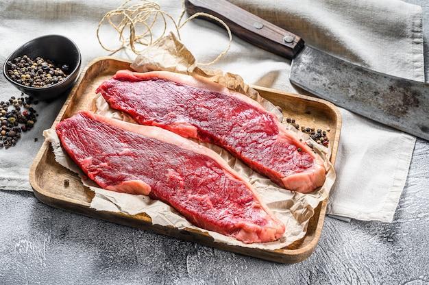 Bife do lombo cru em uma bandeja de madeira com um cutelo. carne de mármore. fundo cinza. vista do topo