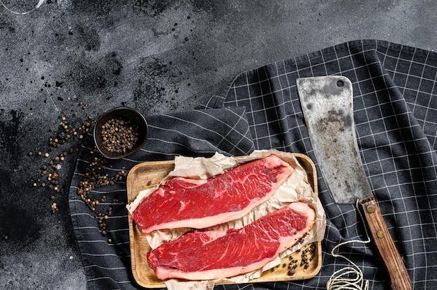 Bife do lombo cru em uma bandeja de madeira com um cutelo. carne de mármore. fundo preto