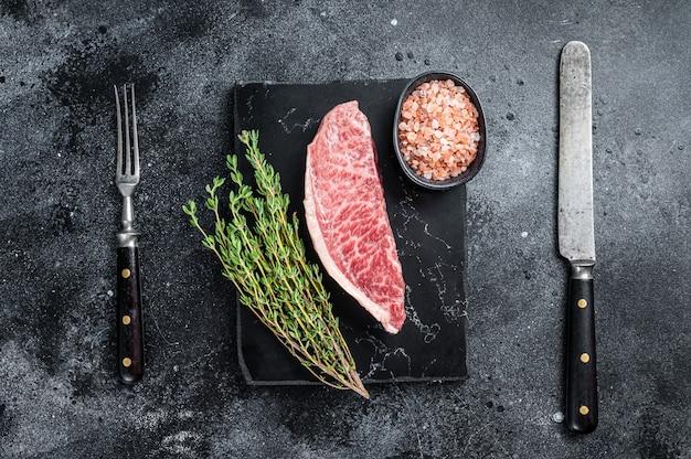 Bife do lombo cru wagyu, carne de boi kobe no tabuleiro de mármore. fundo preto. vista do topo.