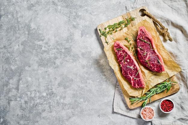 Bife do lombo da carne em uma placa de desbastamento de madeira com alecrins e pimenta cor-de-rosa. copyspace