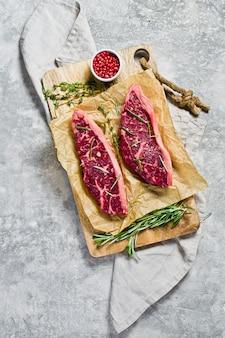 Bife do lombo da carne em uma placa de desbastamento de madeira com alecrins e pimenta cor-de-rosa.