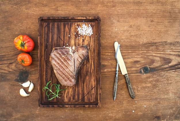 Bife do lombo de carne cozida em servir a placa com dentes de alho, tomate, alecrim e especiarias sobre madeira rústica.