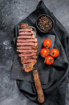 Bife do lombo em fatias grelhadas em um talhador de carne.