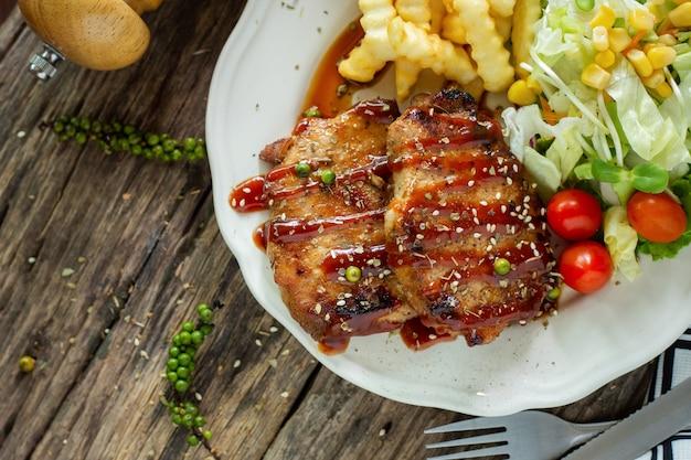 Bife do lombo em um prato em uma mesa de madeira