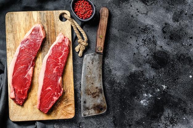 Bife do lombo em uma placa de corte. carne bovina orgânica. fundo preto