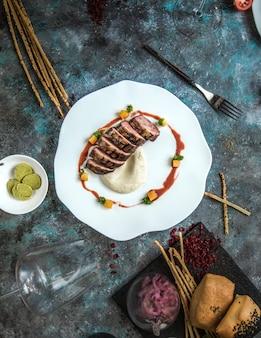 Bife do lombo finamente cozido e cortado, servido com molho tártaro