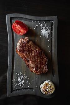 Bife do lombo grelhado servido com alho e tomate na tábua de madeira, vista de cima. orientação retrato
