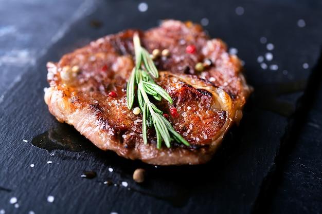 Bife em prato escuro com alecrim e pimenta, foco seletivo