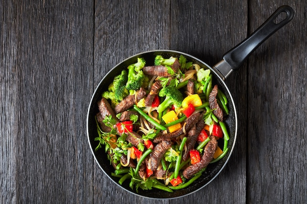 Bife fajita com pimentão amarelo e vermelho, salsa, cebola, feijão verde e brócolis servido em uma frigideira em uma mesa de madeira escura, vista de cima, postura plana, espaço de cópia