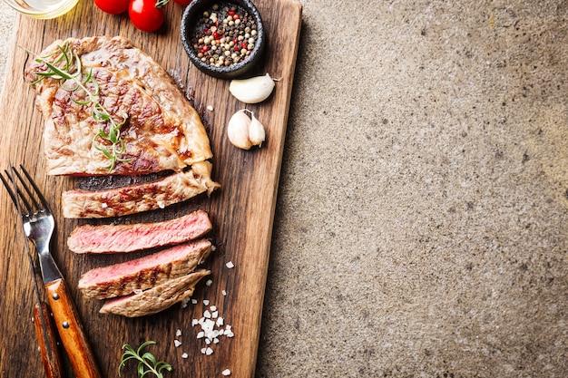 Bife fatiado médio malpassado grelhado em uma tábua rústica com alecrim e especiarias, superfície rústica escura, vista de cima, local para texto