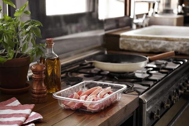 Bife fatiado prestes a ser grelhado em uma panela ao lado de uma cozinha com janela