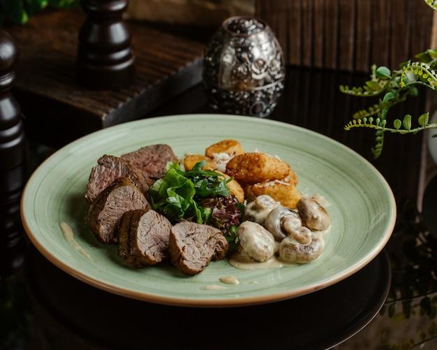 Bife finamente cozido com cogumelos salteados em molho cremoso e batatas assadas