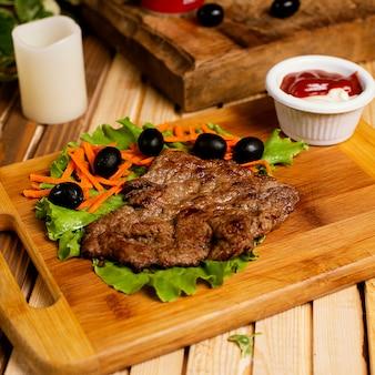 Bife fino servido com maionese de ketchup e salada de legumes.