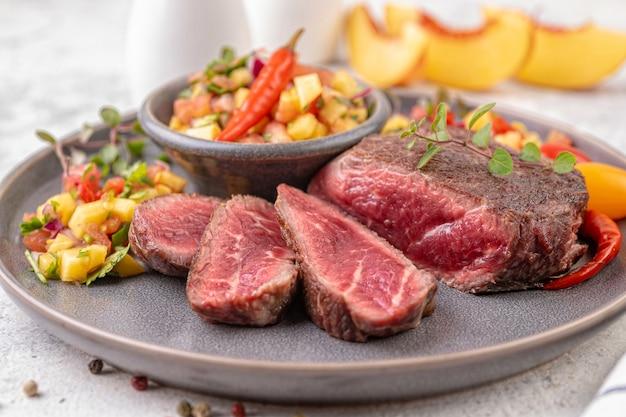 Bife frito com molho de pêssego, tomate e pimenta. bife frito médio ou raro cortado em pedaços. pronto para comer. fechar-se.