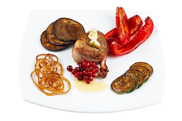 Bife frito em bacon com legumes em um prato. isolado.