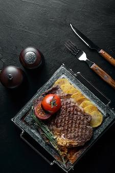 Bife grelhado com faca e garfo esculpido na ardósia de pedra preta. bife em uma pedra de mármore quente.