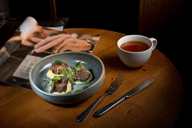 Bife grelhado com legumes purê no prato na mesa de madeira.