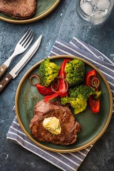 Bife grelhado com manteiga de alho e legumes. carne com pimentão grelhado, brócolis e cebola.