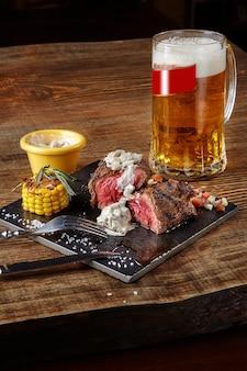 Bife grelhado com milho com molho de cogumelos na tábua e caneca de cerveja na mesa de madeira