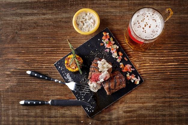 Bife grelhado com milho com molho de cogumelos na tábua e caneca de cerveja na vista de cima da mesa de madeira