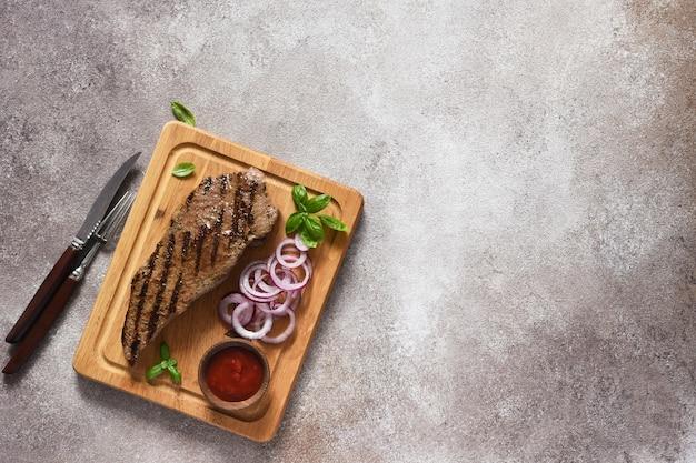 Bife grelhado com molho de tomate e cebola roxa em conserva em uma placa de madeira. vista de cima.