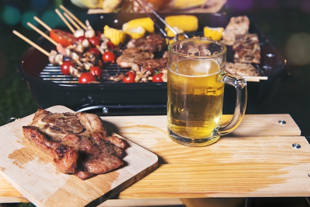 Bife grelhado com tomate e milho na tábua e caneca de cerveja na mesa de madeira