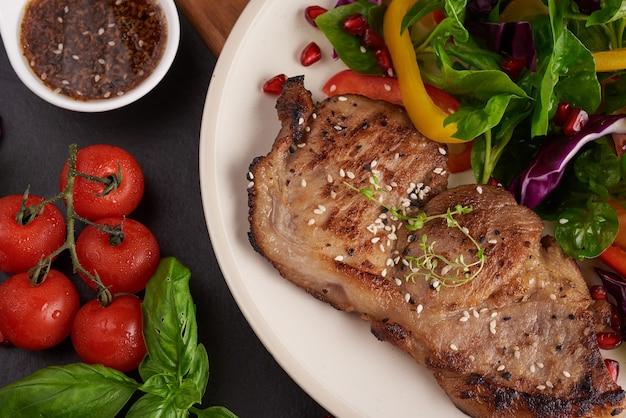 Bife grelhado com vegetais frescos, pimentão, tomate, cebola roxa, pimenta rosa e especiarias. comida saborosa feita em casa. conceito de refeição saborosa e saudável. superfície de pedra preta. bife de porco com salada