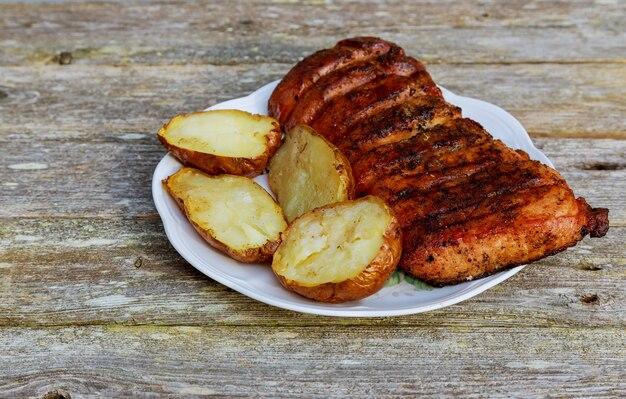 Bife grelhado do roubo com a batata roasted na placa sobre a tabela de madeira.