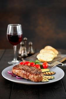 Bife grelhado e abobrinha servido com tomate cereja e manjericão e um copo de vinho tinto