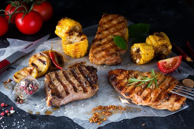 Bife grelhado e legumes, batatas assadas e salada verde no escuro