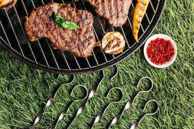 Bife grelhado e legumes com espeto metálico na churrasqueira sobre fundo de grama verde