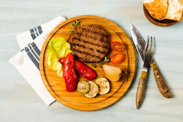 Bife grelhado e legumes servindo na bandeja de madeira