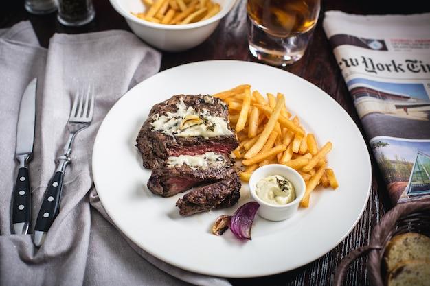 Bife grelhado e mal passado saudável com batata frita, copo de uísque e tempero em boteco ou taverna rústica. estilo de comida