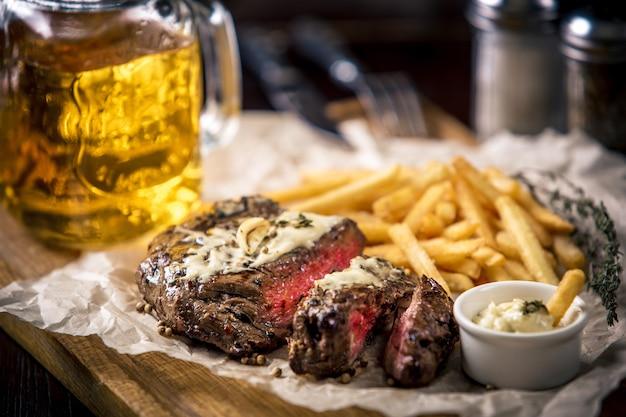 Bife grelhado e mal passado saudável com batata frita e cerveja, além de temperos, em boteco ou taverna rústica. estilo de comida