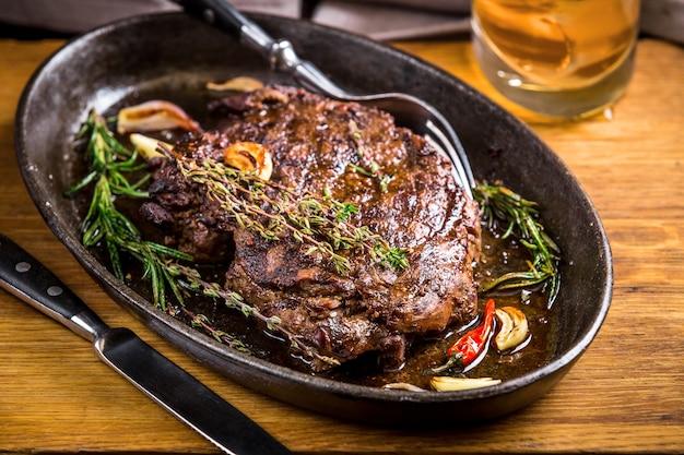 Bife grelhado e mal passado saudável e vegetais com copo de uísque e tempero em boteco ou taverna rústica. estilo de comida