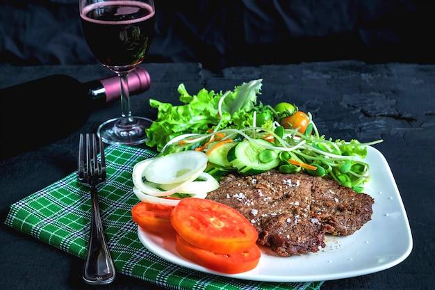 Bife grelhado e vinho tinto na mesa
