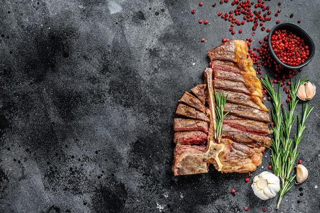 Bife grelhado em fatias. carne bovina cozida com espinha. fundo preto. vista do topo. copie o espaço.