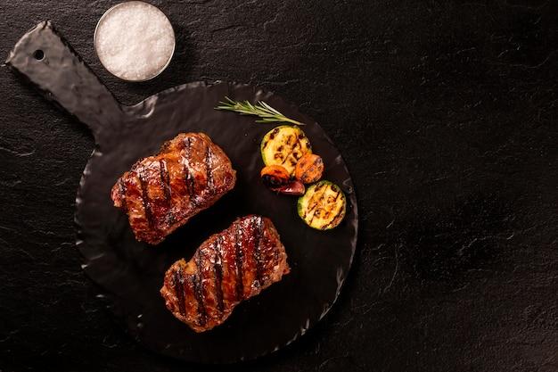 Bife grelhado em fatias de carne na tábua na placa preta sobre a mesa de madeira.